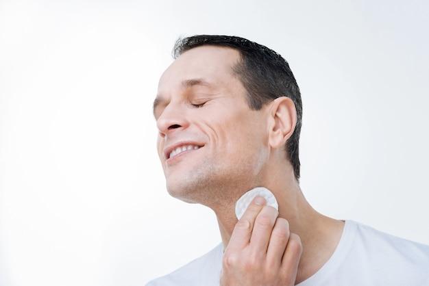 Huidverzorging. vrolijke vreedzame knappe man die zijn ogen sluit en zijn huid reinigt tijdens het gebruik van een wattenschijfje