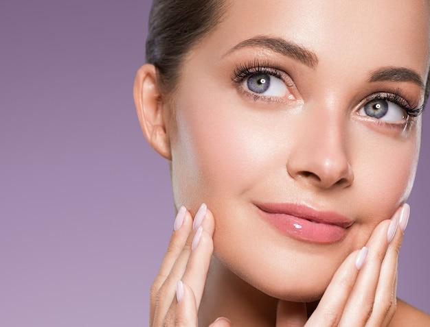 Huidverzorging vrouw schoonheid gezicht gezond gezicht huid cosmetisch model emotioneel en blij met handen