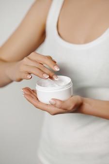 Huidverzorgingsconcept. mooie vrouw met handcrème, lotion op haar handen. close-up foto van vrouwelijke handen cosmetische crème toe te passen op een zachte huid. schoonheidsconcept
