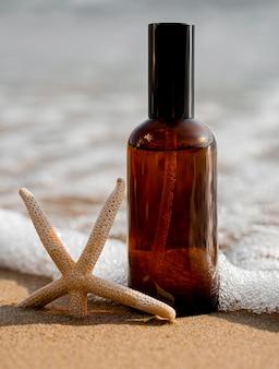 Huidverzorgingsproduct in zand naast oceaan