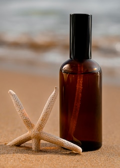 Huidverzorgingsproduct in zand naast oceaanclose-up