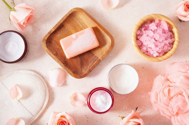 Huidverzorgingsproducten en roze bloemen. natuurlijke cosmetica voor thuisbehandeling