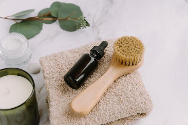Huidverzorgingsproducten lichaams- of gezichtsborstel en serumfles op beige handdoek aroma kaars en crème