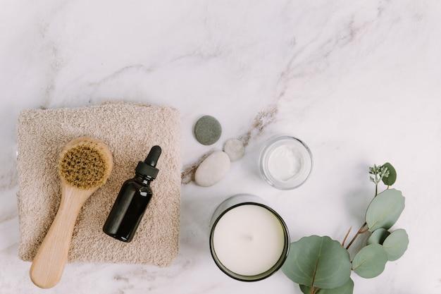 Huidverzorgingsproducten plat lichaam of gezichtsborstel en serumfles op beige handdoek aroma kaars