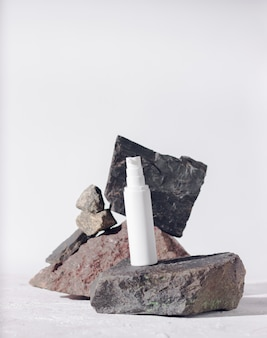 Huidverzorgingsproducten witte plastic fles met dispenser en flacons op stenen achtergrond geïsoleerd