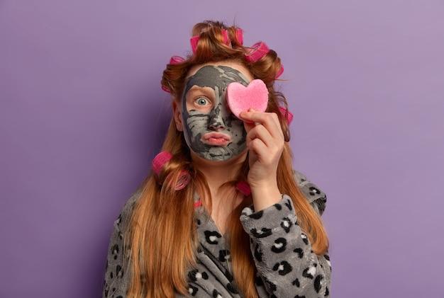 Huidverzorgingsroutine. gembermeisje draagt haarkrulspelden, past voedende klei gezichtsmasker toe voor een gladde huid, bedekt oog met cosmetische spons, gekleed in jurk, doet schoonheidsbehandelingen thuis.