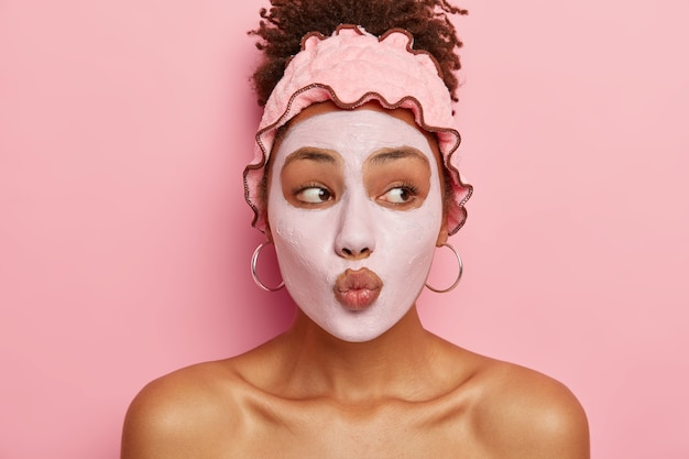 Huidverzorgingsroutine. mooie afro-amerikaanse dame houdt de lippen rond, brengt een voedend masker op het gezicht aan, verkleint de kans op acne, krijgt weinig plezier in het leven van schoonheidsbehandelingen, verbetert de huid