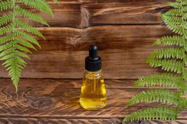 Huidverzorgingsserum in druppelflesje op een houten bord met varenbladeren. spa natuurlijk biologisch schoonheidsproduct verpakkingsontwerp.