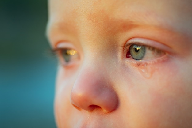 Huilbaby met hemelsblauwe ogen. kleine tedere babyjongen huilen. oogdruppel, traan van een klein lief kind. emotionele baby mist zijn moeder. jeugd concept.