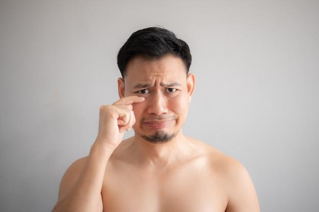 Huilen en verdrietig gezicht van aziatische man in topless portret geïsoleerd op een grijze achtergrond.