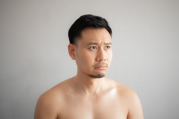 Huilen en verdrietig gezicht van aziatische man in topless portret geïsoleerd op een grijze achtergrond