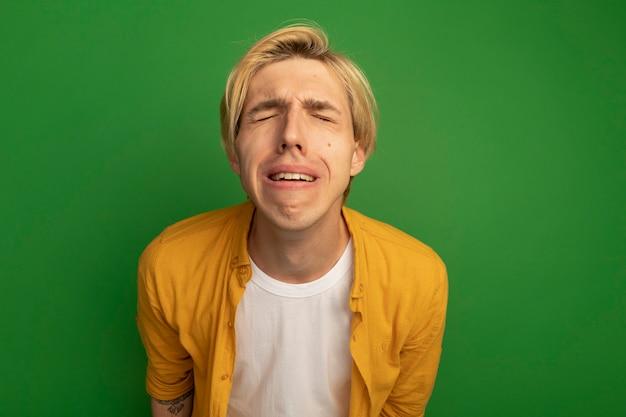Huilen met gesloten ogen jonge blonde man met gele t-shirt geïsoleerd op groen met kopie ruimte