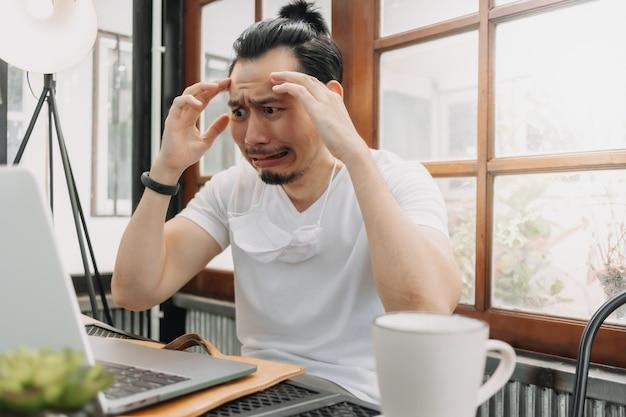 Huilend en geschokt grappig gezicht van de mens stelt zijn werk op zijn laptop teleur