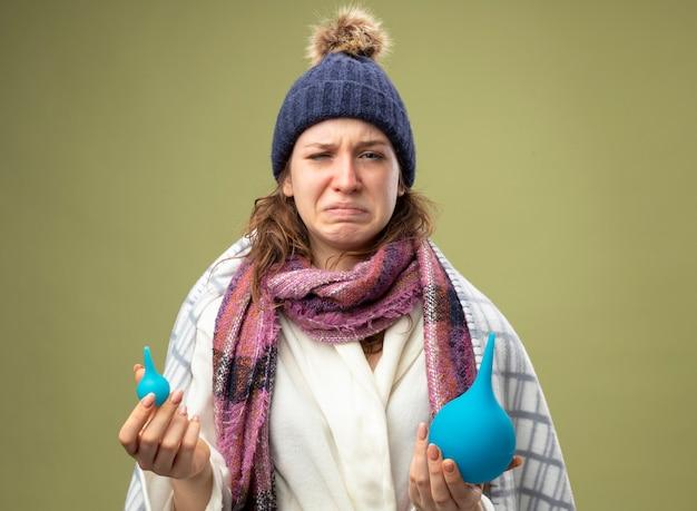 Huilend jong ziek meisje dragen witte mantel en winter hoed met sjaal verpakt in plaid bedrijf klysma's geïsoleerd op olijfgroen