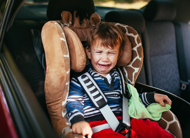 Huilende babyjongen in autostoeltje