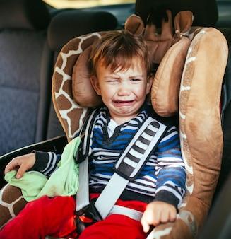 Huilende babyjongen in een veiligheidsautozetel