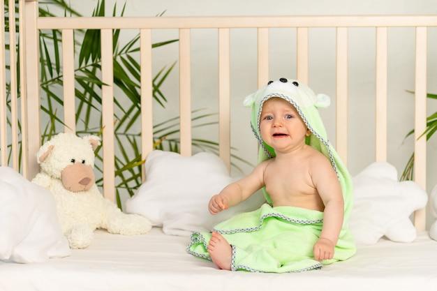 Huilende babyjongen in groene handdoek na bad op bed thuis