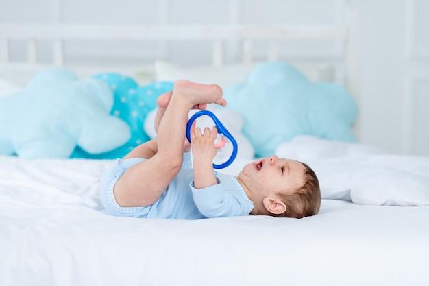 Huilende babyjongen met een rammelaar op het bed om te slapen in een blauwe romper