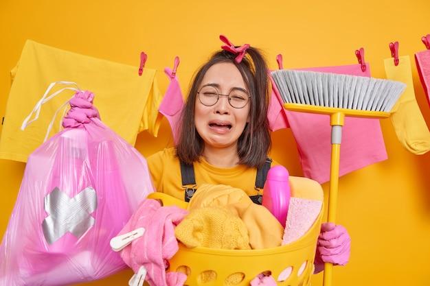 Huilende gefrustreerde aziatische vrouw houdt polyethyleen zak met fles wasmiddel bezem voor het vegen van de vloer heeft uitgeput neerslachtige uitdrukking draagt ronde bril rubberen handschoenen doet de was thuis