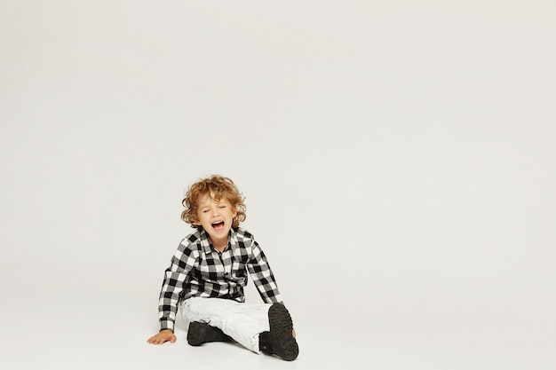 Huilende gekrulde kleine jongen zit op de grond en houdt de hand op zijn been. een klein kind brak zijn been, geïsoleerd over een grijze muur