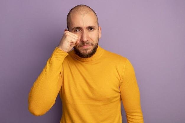 Huilende jonge knappe kerel afvegende oog met hand geïsoleerd op paarse muur