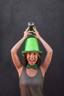 Huilende jonge vrouw in saint patricks hoed bedrijf glas drinken