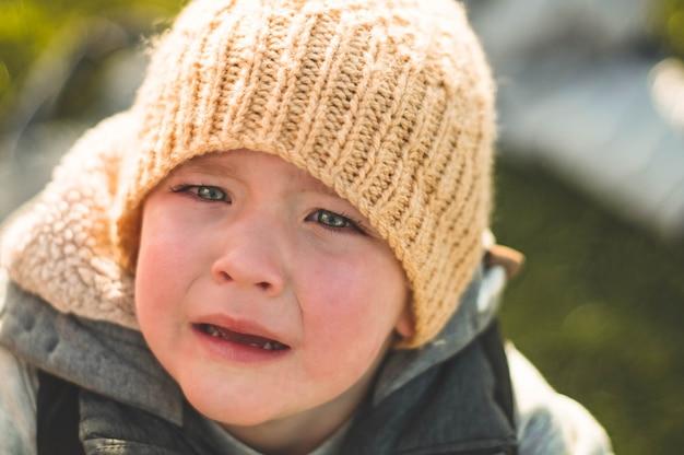 Huilende kleine jongen. huilen. portret van jongen. blanke kind kijkt naar de camera. charmante jongen, het joch huilt met tranen in zijn ogen