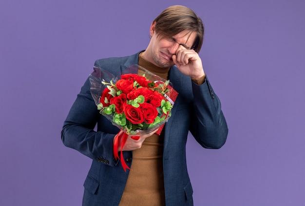 Huilende knappe slavische man met geschenkdoos en boeket bloemen op valentijnsdag