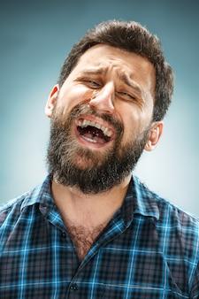 Huilende man in blauw shirt