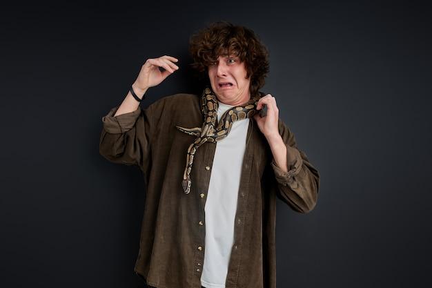 Huilende man is bang voor een slang die zich om zijn nek wikkelt, schreeuwt geïsoleerd op zwarte muur