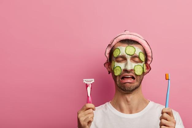 Huilende ontevreden man met vochtinbrengende komkommers en gezichtsmasker, moe van schoonheidsbehandelingen, houdt scheermes en tandenborstel vast