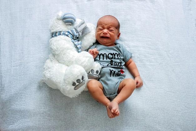 Huilende pasgeboren baby. heel schattig klein jongetje op het bed met speelgoed van een grote beer