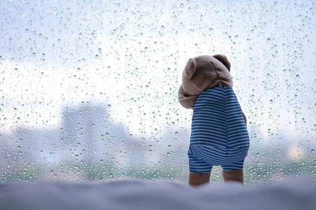 Huilende teddybeer bij het raam in regenachtige dag.