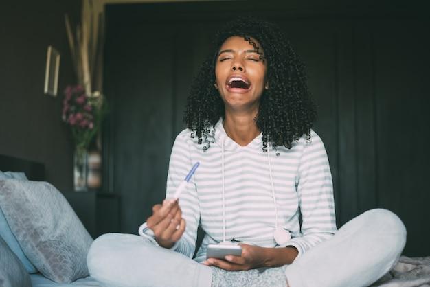 Huilende, verdrietige en bezorgde zwarte vrouw met zwangerschapstest in bed