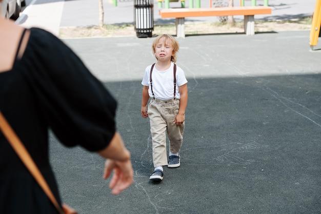 Huilende vierjarige jongen die op asfalt naar zijn moeder loopt voor knuffels en troost. van achter de vrouw, schouder.