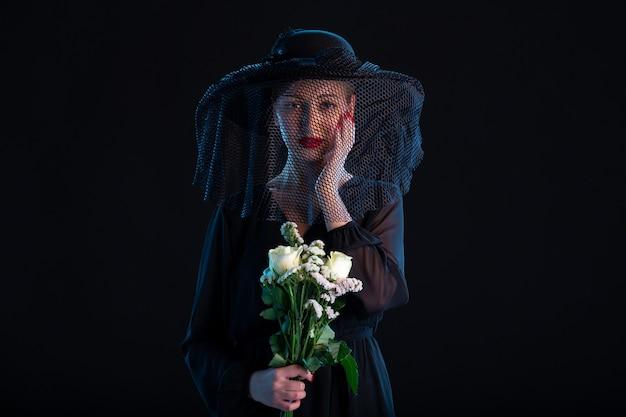 Huilende vrouw gekleed in het zwart met bloemen op de begrafenis van de zwarte dood verdriet