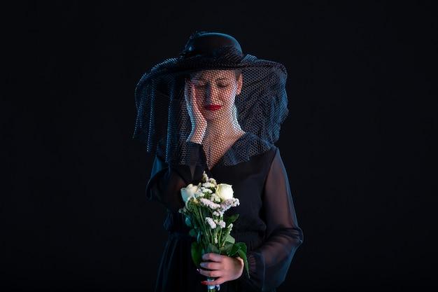Huilende vrouw gekleed in het zwart met bloemen op de begrafenis van de zwarte dood