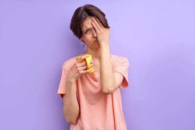 Huilende vrouw heeft meer rust nodig vrouw is moe van het werk wil niet gaan werken of studeren met mok of beker in handen geïsoleerde paarse achtergrond