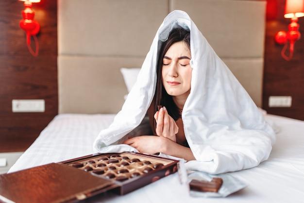 Huilende vrouw ligt in bed onder de deken en eet snoep, vrouwelijke depressie concept. benadrukt meisje dat een probleem heeft