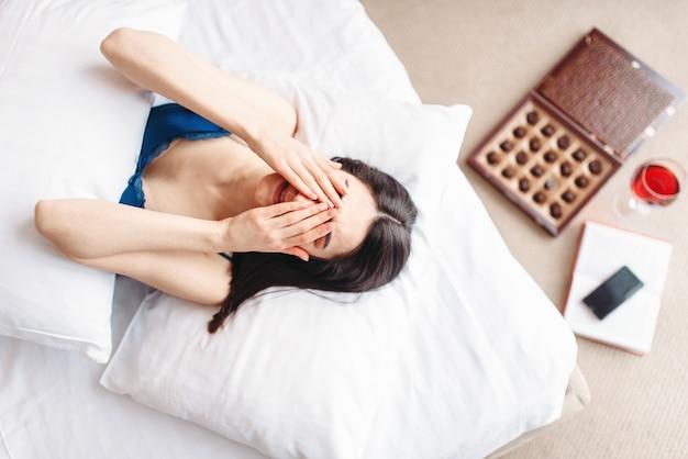 Huilende vrouw ligt in bed onder de deken, snoepdoos en tv-afstandsbediening