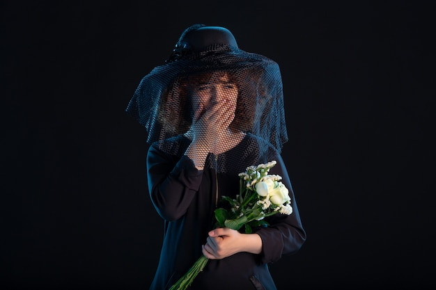Huilende vrouw met bloemen gekleed in het zwart op zwart bureau begrafenis dood verdriet