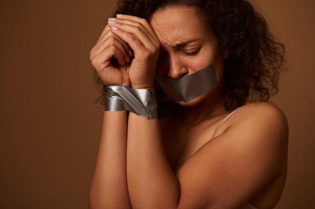 Huilende vrouw met tranen in haar gesloten ogen met gebonden handen en verzegelde mond, neerkijkend met hopeloosheid, geïsoleerd op een donkere achtergrond met kopieerruimte. concept van eliminatie van geweld tegen vrouwen