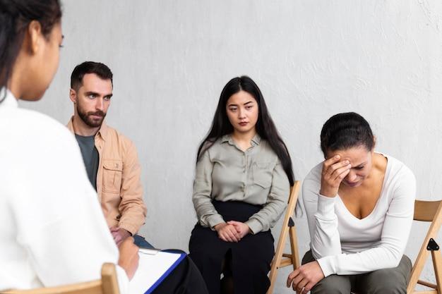 Huilende vrouw tijdens een groepstherapie-sessie