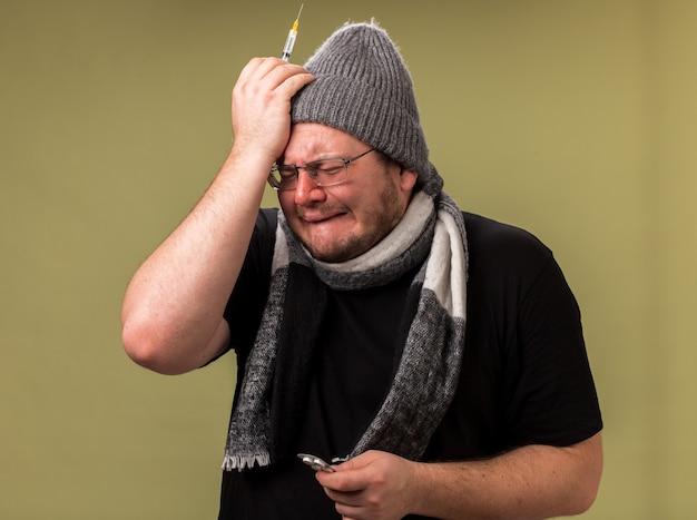 Huilende zieke man van middelbare leeftijd met een wintermuts en sjaal met een spuit met pillen die de hand op het voorhoofd legt