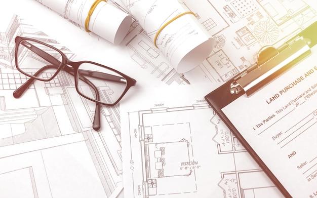 Huis bouwen op blauwdrukken, bouwproject. werken aan bouwconstructies. kantoortafel met klembord en zwarte bril