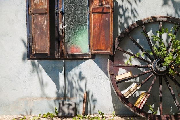 Huis buitenkant met planten en oud wiel