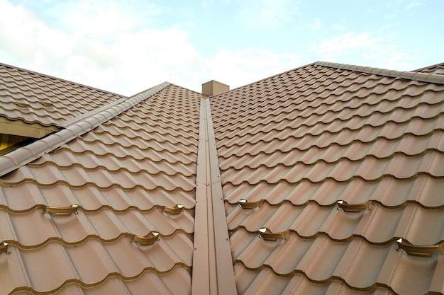 Huis dakoppervlak bedekt met bruine metalen tegelplaten.