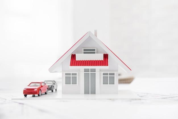 Huis- en automodel met plattegronden voor een onroerendgoedproject op tafel.