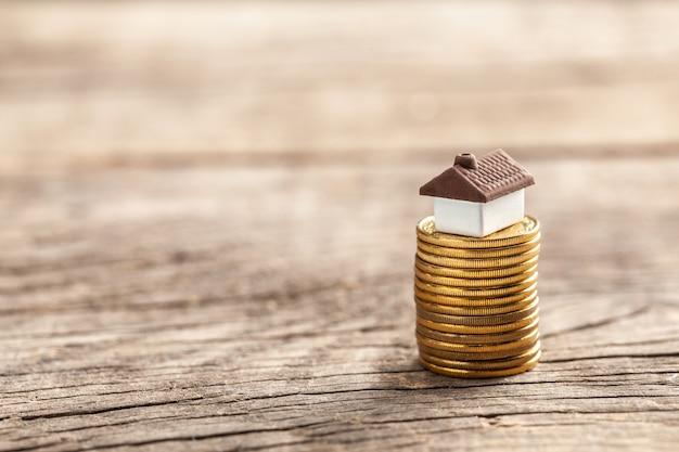 Huis en een stapel munten. de marktprijs van het huis. groei van de vastgoedmarkt.