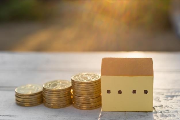 Huis en gouden munten op houten tafel met onscherpe achtergrond, eigenschappen concept